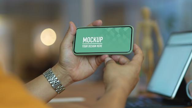 Close-up van mannelijke handen met mock up horizontale smartphone Premium Psd