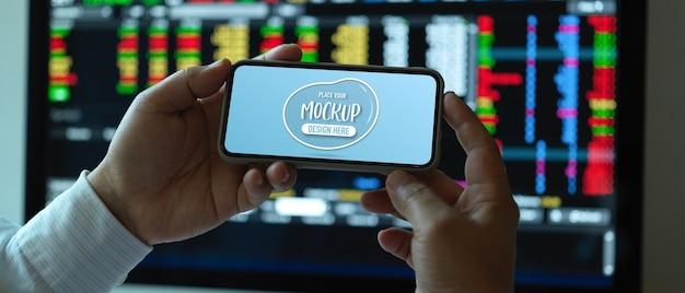 Close-up van mannelijke kantoormedewerker mock up horizontale smartphone op bureau te houden Premium Psd
