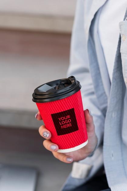 Close-upvrouw die een kop van koffiemodel houden Gratis Psd