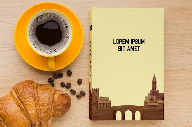 Composición de portada de libro sobre fondo de madera con taza de café PSD gratuito