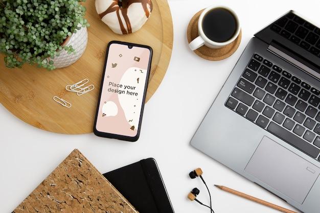 Concepto de escritorio de vista superior con teléfono inteligente PSD gratuito
