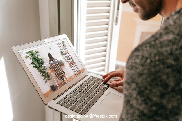 Concepto de oficina en casa con hombre mirando a portátil PSD gratuito