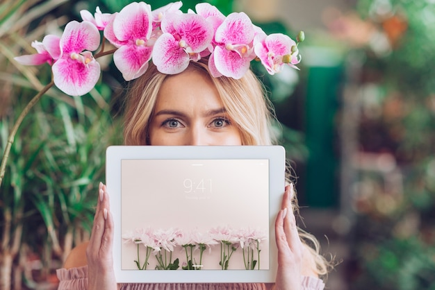Concepto de primavera con mujer sujetando maqueta de tableta PSD gratuito