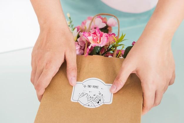 Concetto di giardinaggio con la borsa della tenuta della donna con i fiori Psd Gratuite