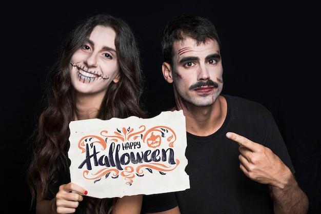 Coppia la carta della tenuta con lettering di halloween Psd Gratuite