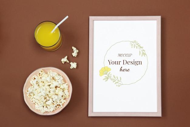 Cornice per foto modello con bicchiere di succo e popcorn su sfondo marrone Psd Premium