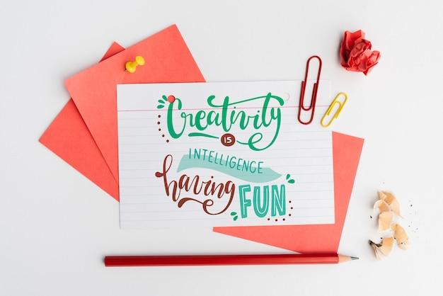Creativiteit is intelligentie met pleziercitaat op wit papier met schrijfwaren Gratis Psd
