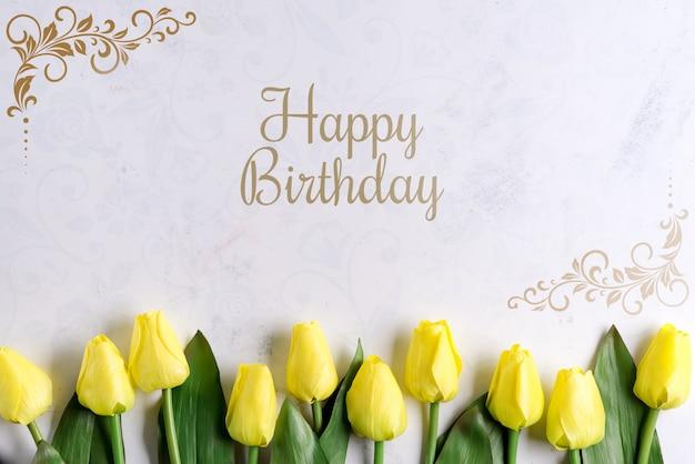 De gelukkige bloemen van de verjaardags gele tulp op vlakke steenachtergrond, leggen met exemplaarruimte Premium Psd