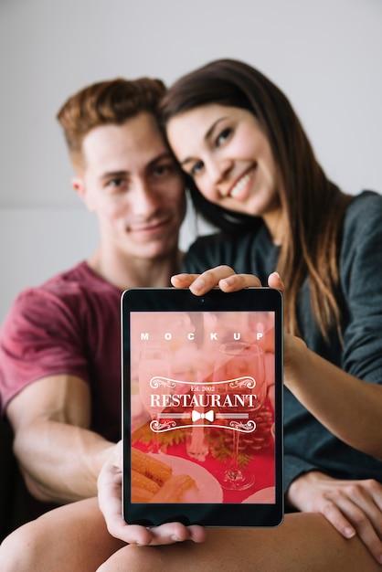 De tabletmodel van de paarholding voor valentijnskaart Gratis Psd