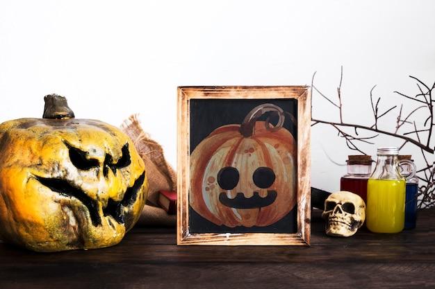 Decorazione dello scrittorio di halloween con il ritratto intagliato della zucca Psd Gratuite