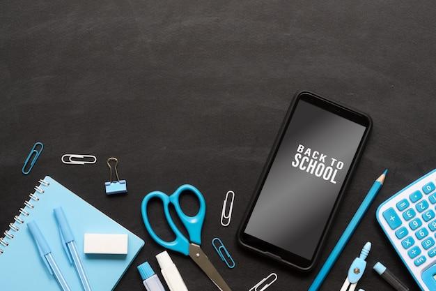 Derida sul telefono cellulare per di nuovo al concetto del fondo della scuola. oggetti della scuola sul fondo di struttura della lavagna del nero di lerciume con lo smartphone del modello Psd Premium