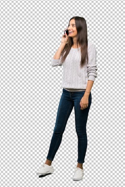 Un disparo de cuerpo entero de una joven morena hispana manteniendo una conversación con el teléfono móvil PSD Premium