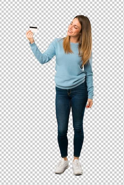 Donna bionda con la camicia blu che tiene una carta di credito e pensando Psd Premium