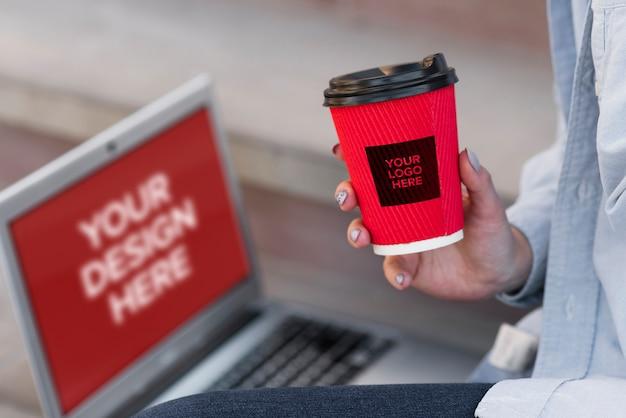 Donna che tiene una tazza di caffè mentre sedendosi accanto ad un modello del computer portatile Psd Gratuite