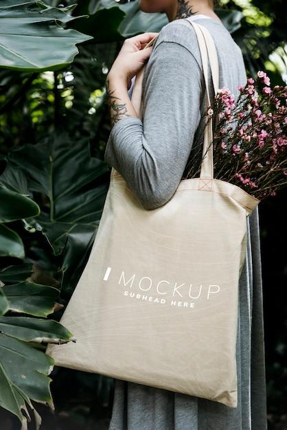 Donna che trasporta un tote bag mockup con fiori Psd Premium
