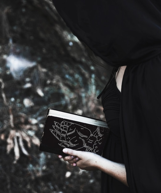 Donna con cappuccio nero leggendo da un libro degli incantesimi Psd Gratuite
