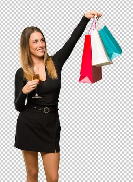 Donna con champagne festeggia il nuovo anno 2019 in possesso di un sacco di borse per la spesa Psd Premium