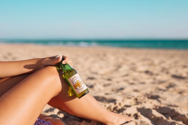 Donna con il modello di bottiglia di birra in spiaggia Psd Gratuite