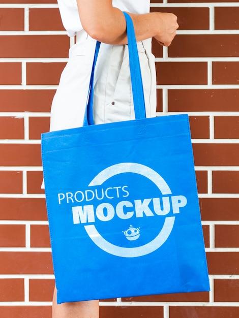 Donna di vista laterale che tiene un modello semplice della borsa blu Psd Gratuite