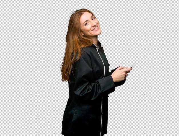 Donna giovane chef di redhead inviando un messaggio con il cellulare Psd Premium