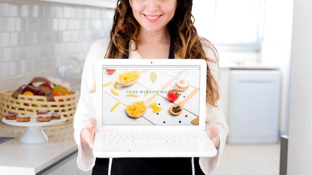 67da987b7009c8 Donna in cucina che presenta il mockup di laptop | Scaricare PSD gratis