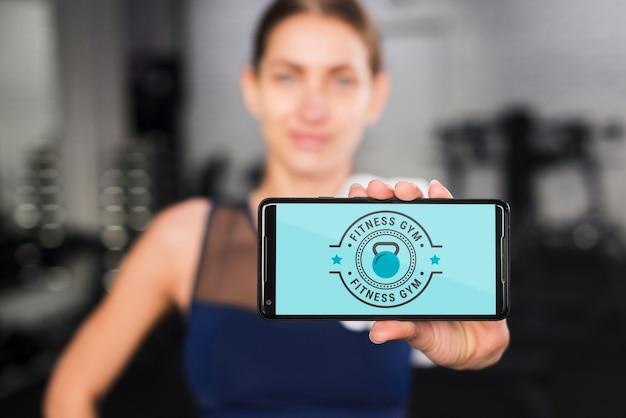 Donna sportiva felice che presenta il modello di smartphone Psd Gratuite