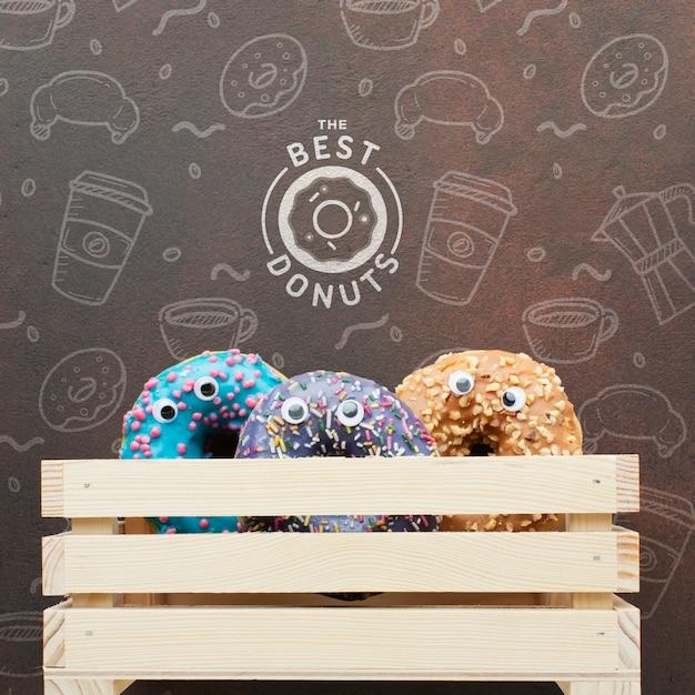Donuts de colores en caja de madera con maqueta PSD gratuito