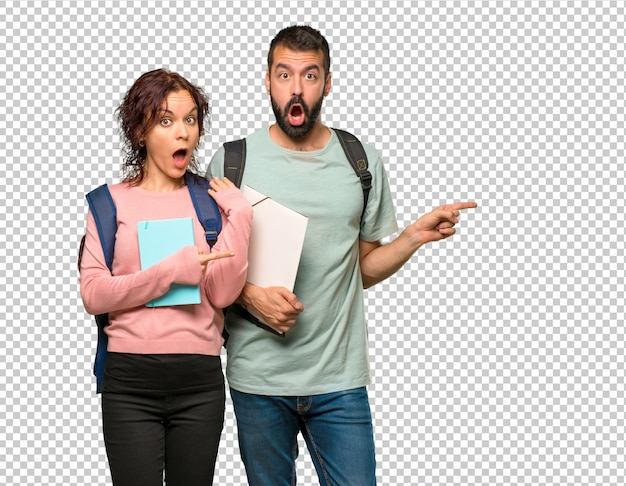 Dos estudiantes con mochilas y libros apuntando con el dedo hacia un lado con una cara sorprendida PSD Premium