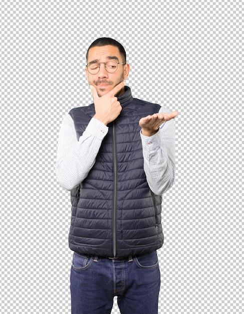 Dudoso joven sosteniendo algo con su mano PSD Premium
