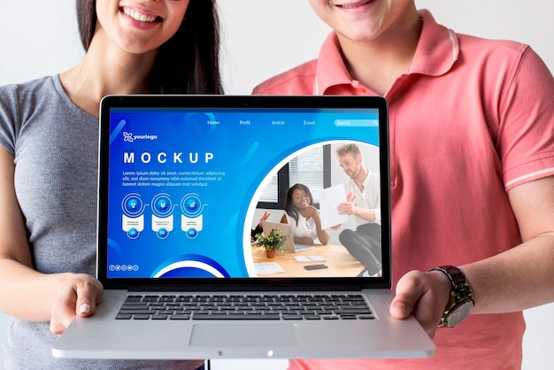 Echtpaar met een mock-up laptop Gratis Psd