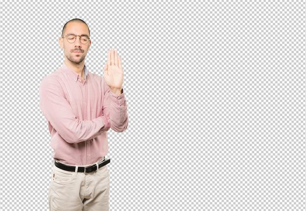 Ernstige jonge mens die een gebaar van einde met zijn palm maakt Premium Psd