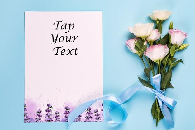 Eustoma flores con hoja de papel en una vista azul, superior. PSD Premium
