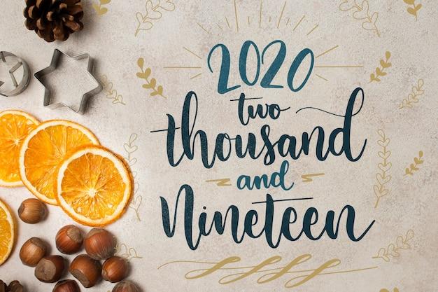 Feliz año nuevo 2020 concepto con rodajas de naranja PSD gratuito