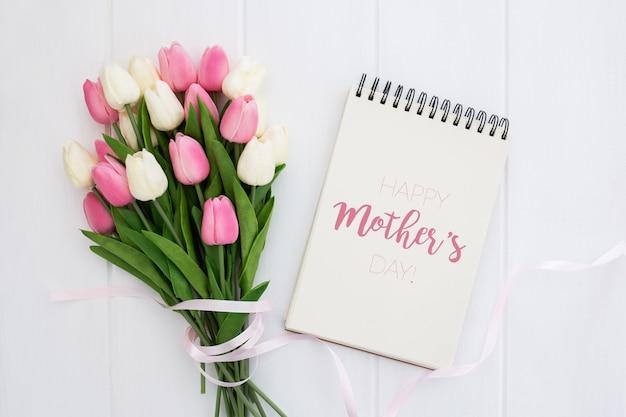 Festa della mamma felice mock up sul notebook con tulipani rosa e bianchi, su fondo di legno bianco Psd Gratuite