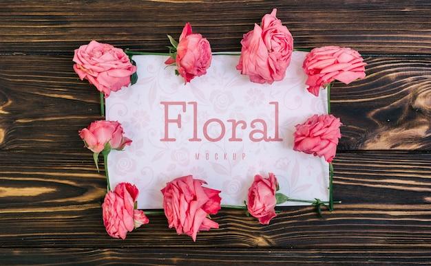 Floral frame roze rozen mockup op houten tafel Gratis Psd