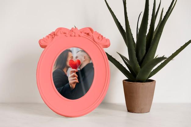 Frame mockup naast een plant Gratis Psd