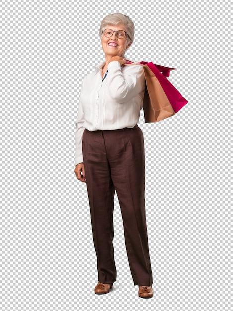 Full body senior vrouw vrolijk en lachend, erg enthousiast met een boodschappentas, klaar om te gaan winkelen en op zoek naar nieuwe aanbiedingen Premium Psd