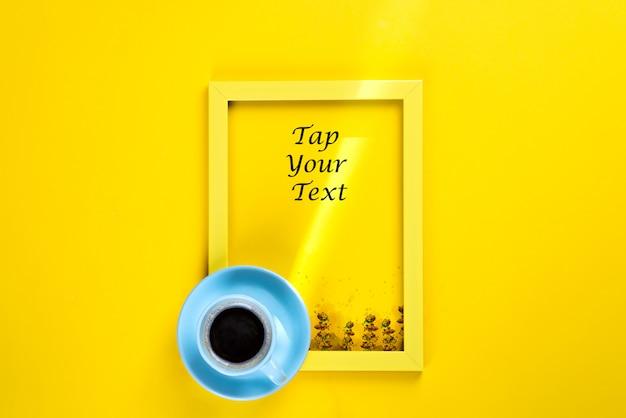 Geel kader met een zonnestraal en een kopje thee erop, bovenaanzicht op een geel papier Premium Psd