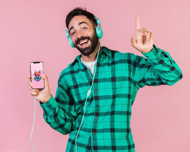 Gelukkig bebaarde man met koptelefoon en mobiele telefoon mock up Gratis Psd