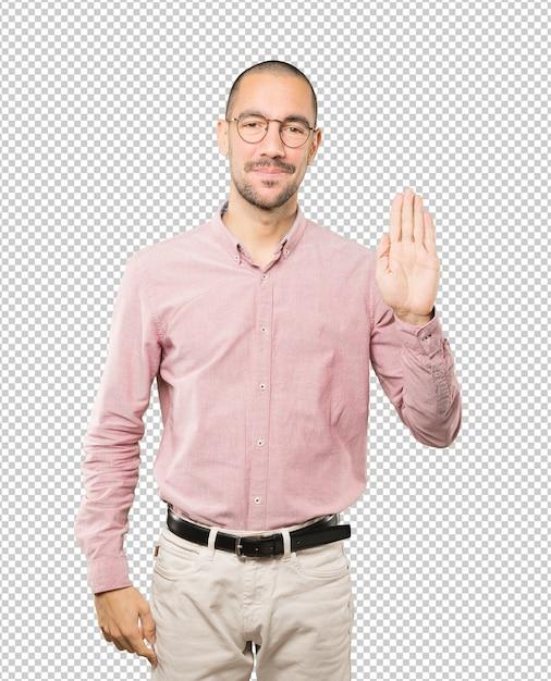 Gelukkig jonge man een gebaar van stop met zijn handpalm maken Premium Psd