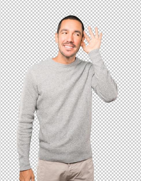Gelukkig jonge man glimlachend en een gebaar maken van iets proberen te horen Premium Psd
