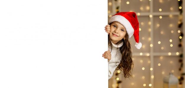 Gelukkig klein kindmeisje die in rode santahoed wit karton houden Premium Psd