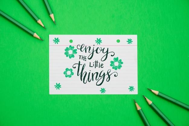 Geniet van het kleine citaat op bloemen witboek en groene achtergrond Gratis Psd