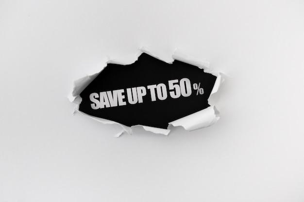 Gescheurde gat in de witte muur van papier op een zwarte achtergrond Gratis Psd