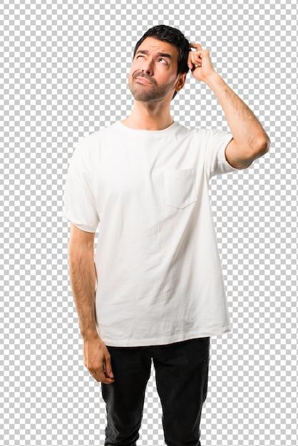 Giovane con la camicia bianca che ha dubbi e con l'espressione faccia confusa mentre grattando la testa Psd Premium