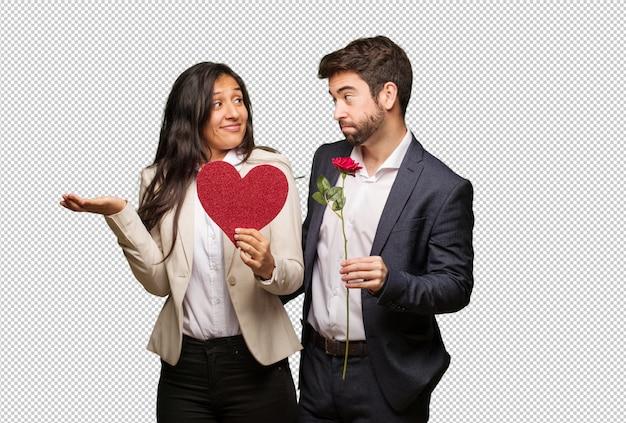 Giovane coppia a san valentino dubitando e alzando le spalle Psd Premium