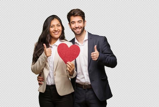 Giovane coppia in giorno di san valentino sorridendo e alzando il pollice in su Psd Premium