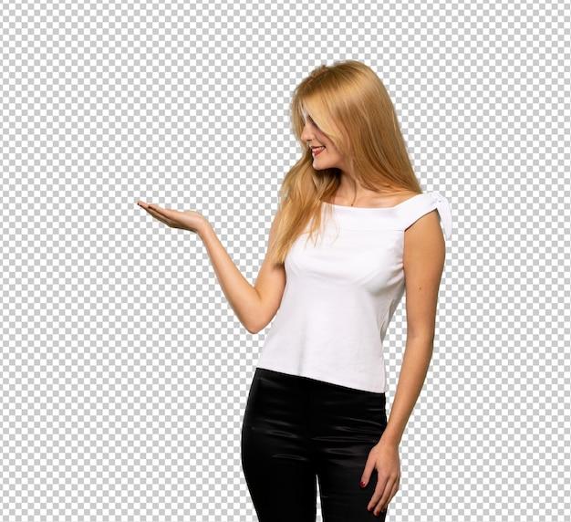Giovane donna bionda che tiene copyspace immaginario sul palmo per inserire un annuncio Psd Premium