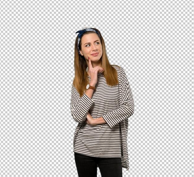 Giovane donna con il foulard che pensa un'idea mentre osserva in su Psd Premium