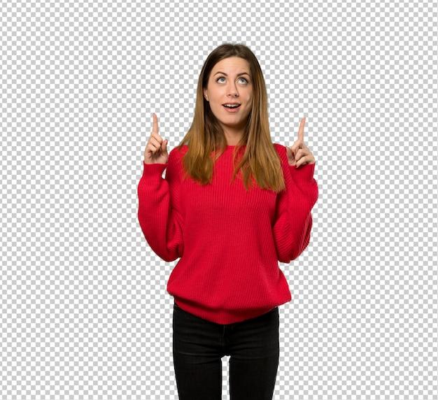 Giovane donna con maglione rosso sorpreso e rivolto verso l'alto Psd Premium